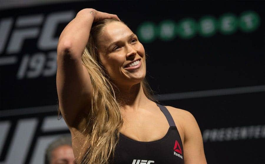 Ronda Rousey in the ring pushing her hair out of her face