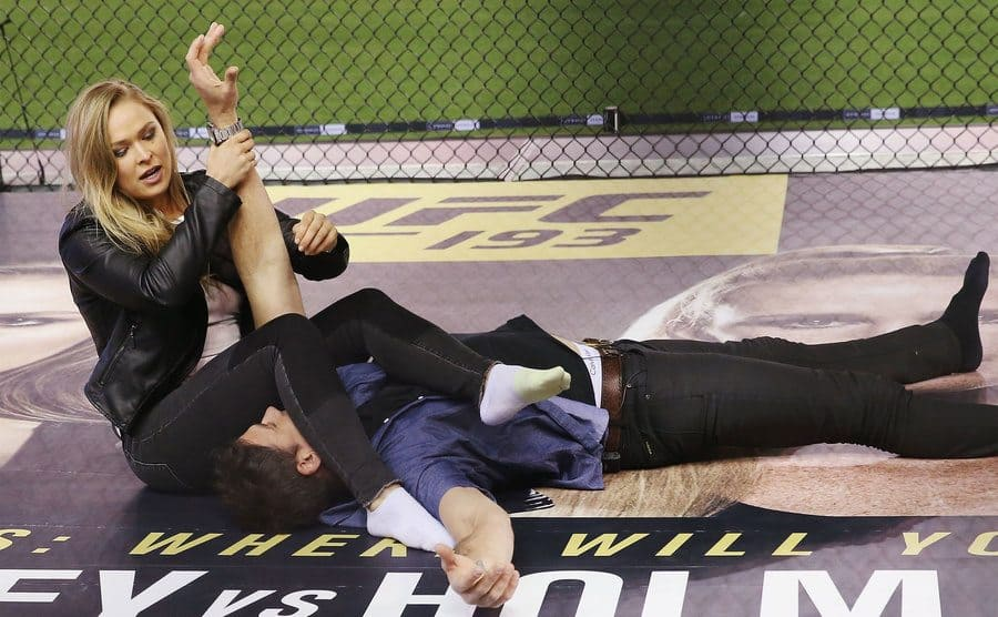 Ronda showing a news reporter a move on the mat