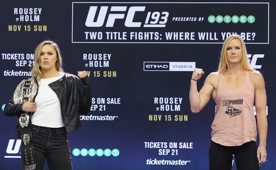 Ronda Rousey and Holly Holm standing with their arm flexed during press interviews