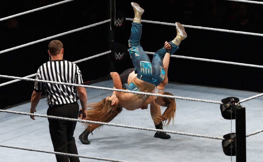 Ronda Rousey and Mickie James mid flip during a match