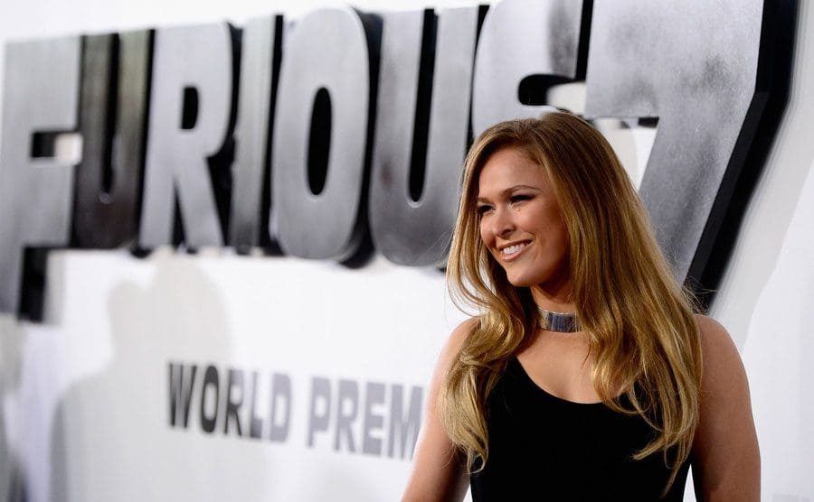 Ronda Rousey on the red carpet in a black dress at the Furious 7 premiere