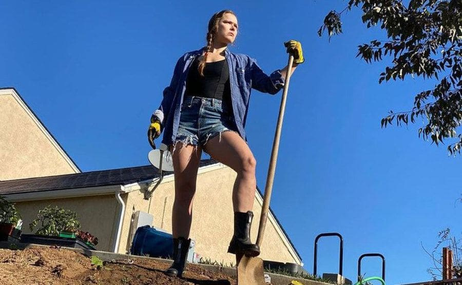 Ronda standing on a shovel with the tip of it in the dirt looking off past the camera