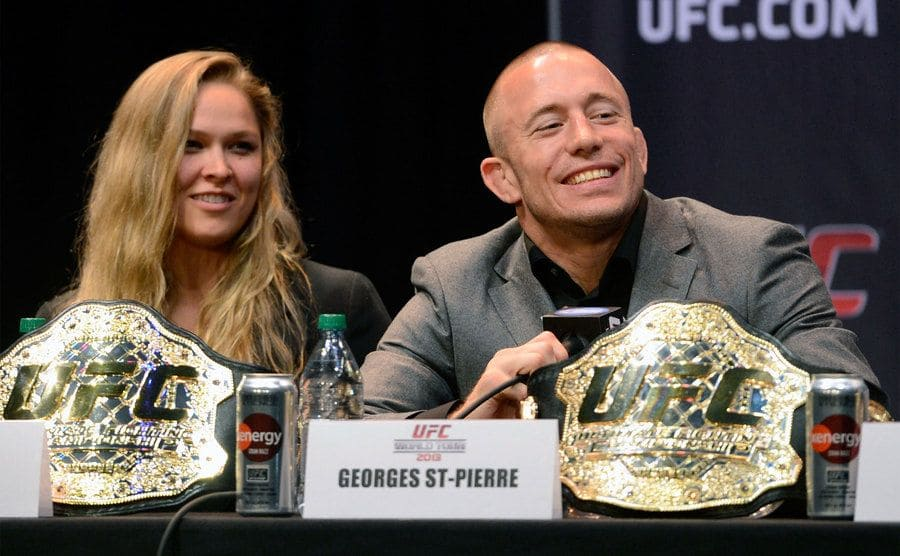 Ronda Rousey and George St. Pierre at a press conference with their belts on the table in front of them