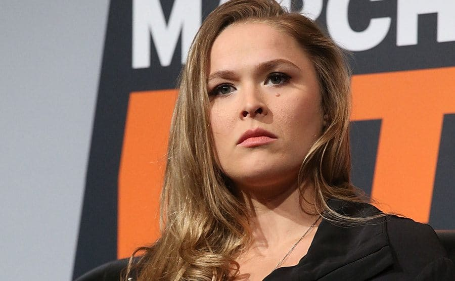 Ronda Rousey sitting on a stage