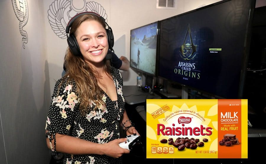Ronda Rousey with a game controller with a logo for Assasins Creed Orgins on the screen / A box of Raisinet chocolates