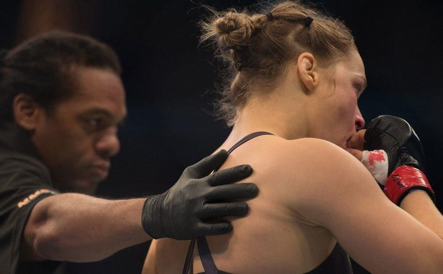 Ronda placing her mouth guard back in
