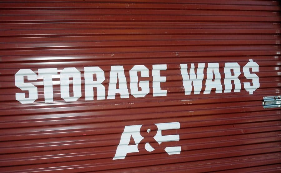 """A closed storage locker door with the """"Storage Wars"""" and A&E logos drawn on it."""