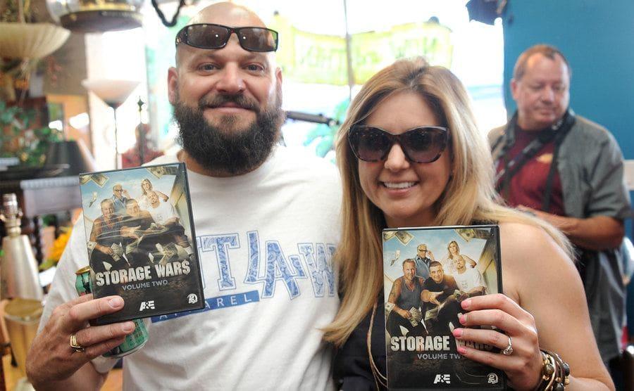 "Jarrod Schulz and Brandi Passante holding up DVD boxes of ""Storage Wars."""