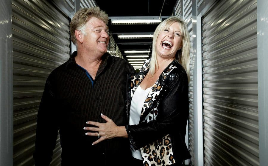 Dan and Laura Dotson standing in a storage facility hallway while Laura lets out a great big laugh.