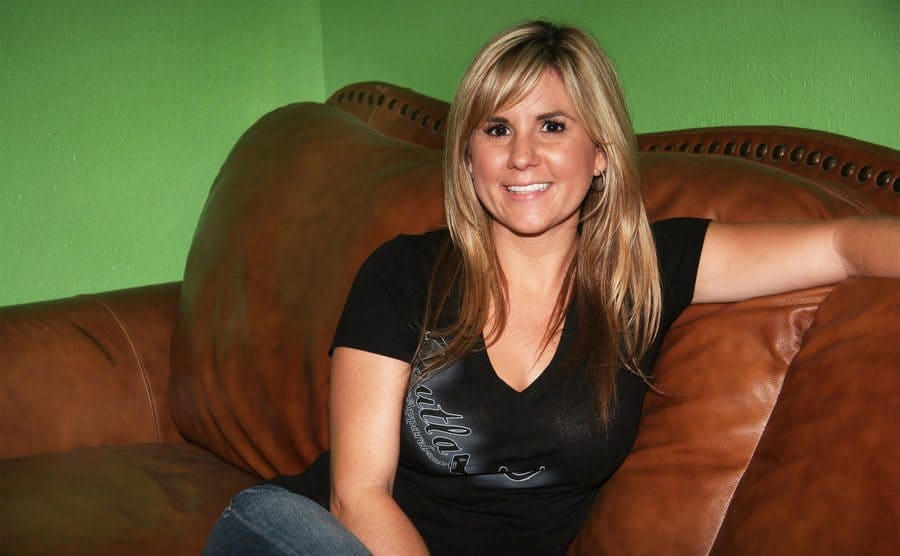 Brandi Passante sitting on a brown leather couch.