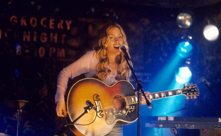Piper Perabo singing and playing the guitar on stage in a scene from Coyote Ugly
