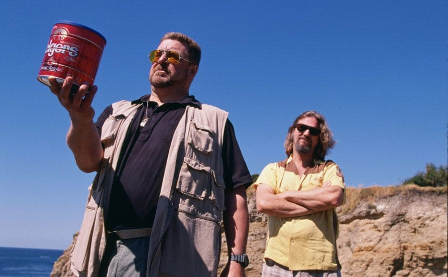John Goodman holding a large can of folgers coffee with Jeff Bridges standing behind him on a cliff near the ocean in a scene from The Big Lebowski