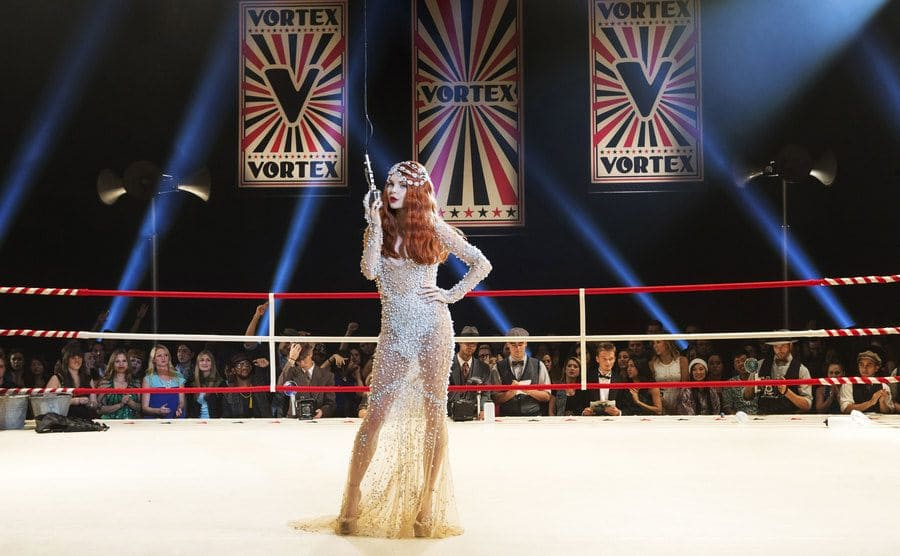 Izabella Miko standing dressed in a fancy gown standing with the microphone in the middle of a boxing ring in a scene from Step Up All In