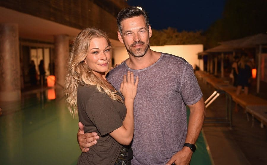 LeAnn Rimes and Eddie Cibrian posing in a backyard event next to a pool