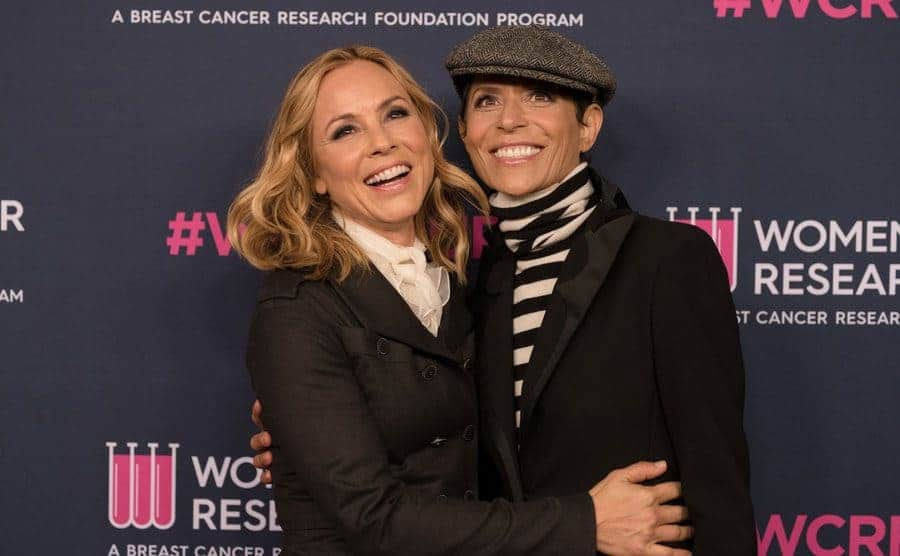 Maria Bello and her partner Dominque Crenn posing on the red carpet for event arrivals