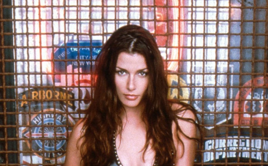 Bridget Moynahan posing in front of a barred window in Coyote Ugly