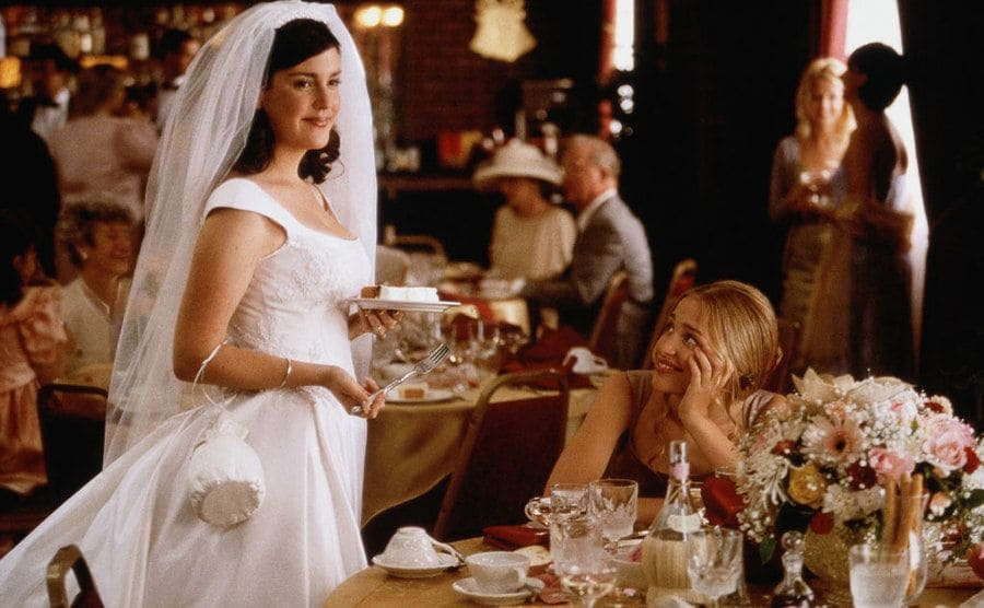 Melanie Lynskey in a wedding dress bringing a piece of cake to Piper Perabo sitting at a table for guests