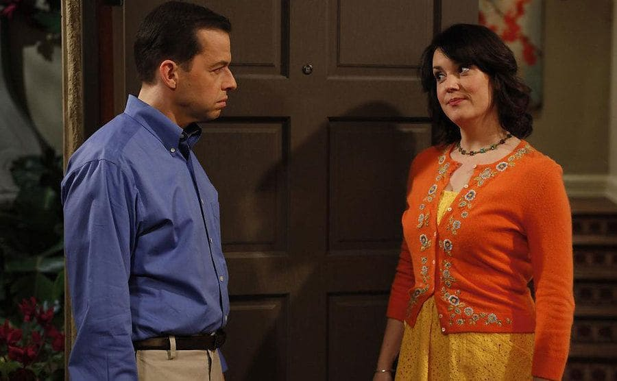 Jon Cryer and Melanie Lynskey standing in a doorway talking in a scene from Two and a Half Men