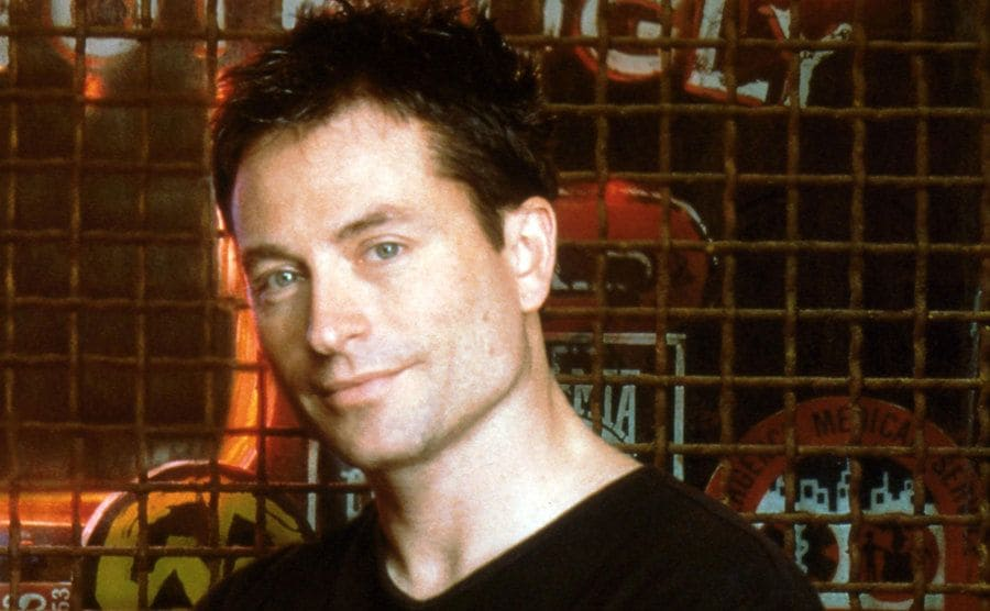 David McNally posing in front of the barred window in a promotional photograph for Coyote Ugly