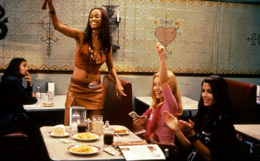 Tyra Banks, Izabella Miko, and Bridget Moynahan motioning to someone in the distance while hanging around a table at a diner