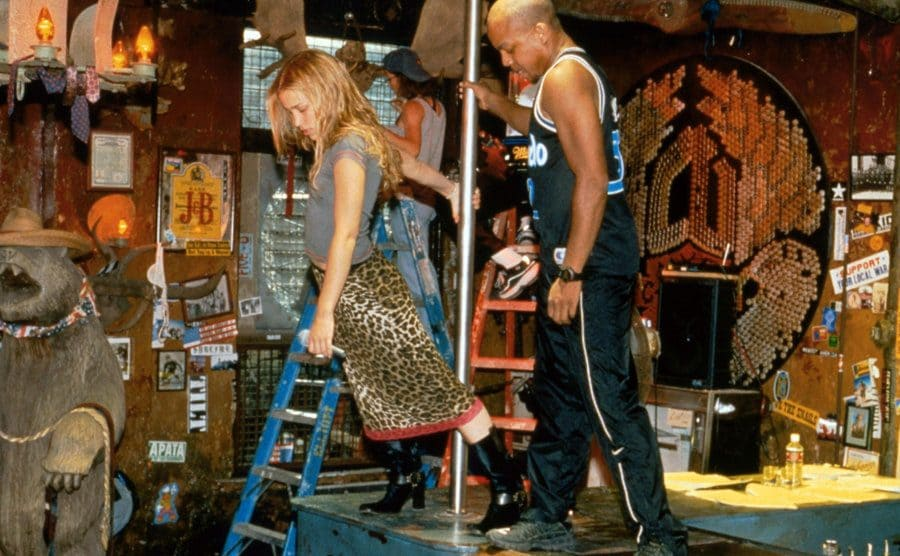 Piper Perabo practicing dancing on a pole on the sets stage