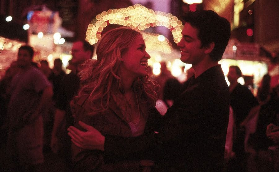 Piper Perabo and Adam Garcia outdoors with places lit up around them