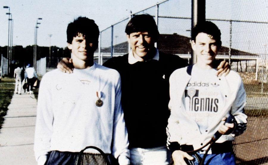 Jose Menendez with Lyle and Erik posing next to the tennis courts at Princeton University