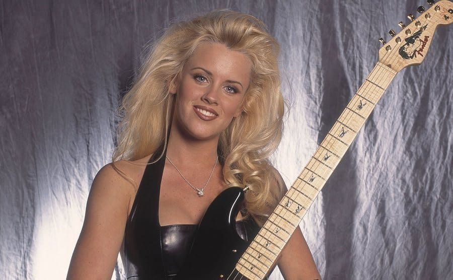 Jenny McCarthy holding a guitar posing in front of a grey background