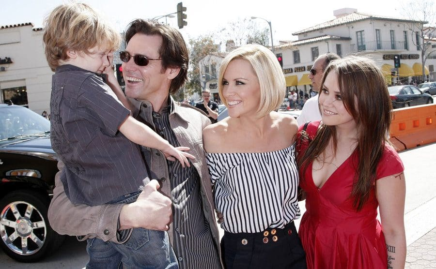Jim Carrey holding Jenny's son while posing with Jenny McCarthy and his daughter Jane Carrey