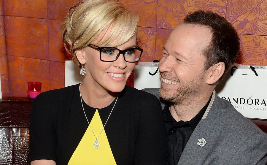 Jenny McCarthy and Donnie Wahlberg sharing a joke sitting together on a couch