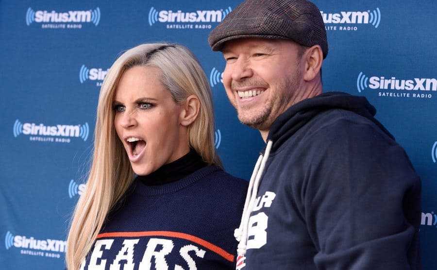 Jenny McCarthy with her mouth open in shock posing with Donnie Wahlberg on the red carpet