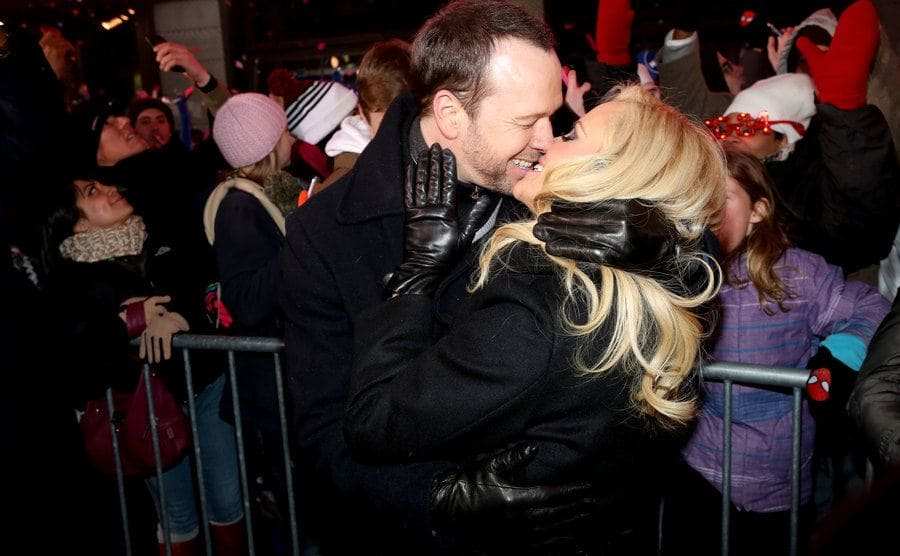 Donnie Wahlberg and Jenny McCarthy kissing in front of a group of people
