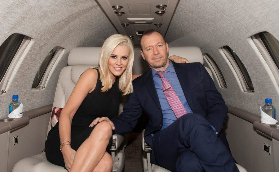 Jenny McCarthy and Donnie Wahlberg sitting in a private jet