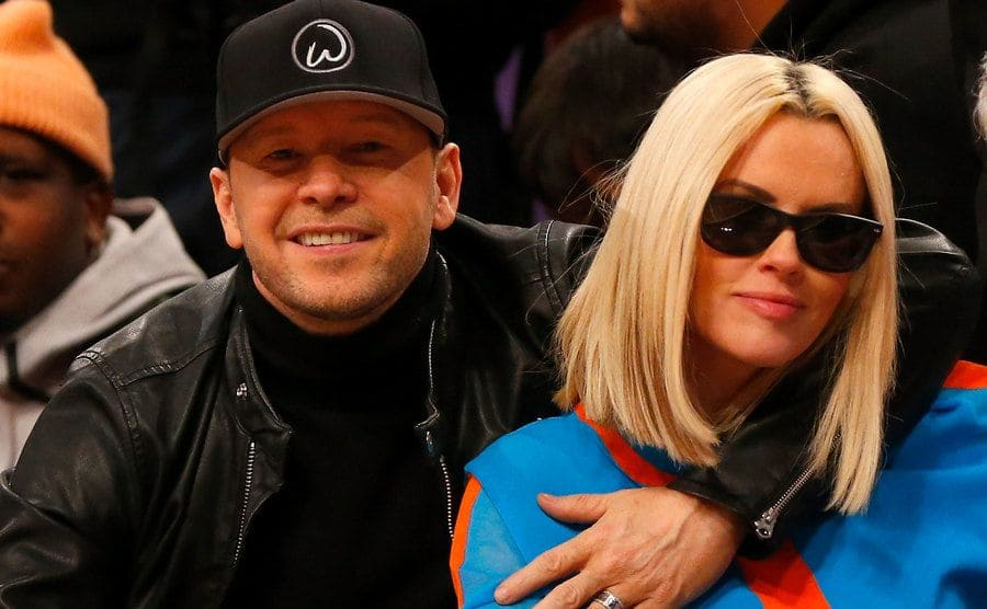 Donnie Wahlberg and Jenny McCarthy posing courtside at a Celtics game
