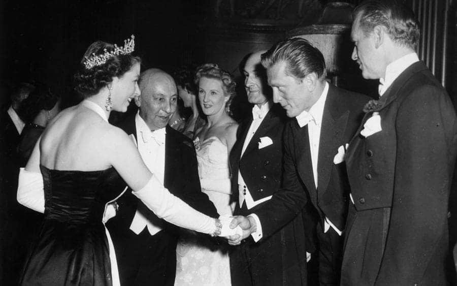 Kirk Douglas bows and shakes hands with Queen Elizabeth II