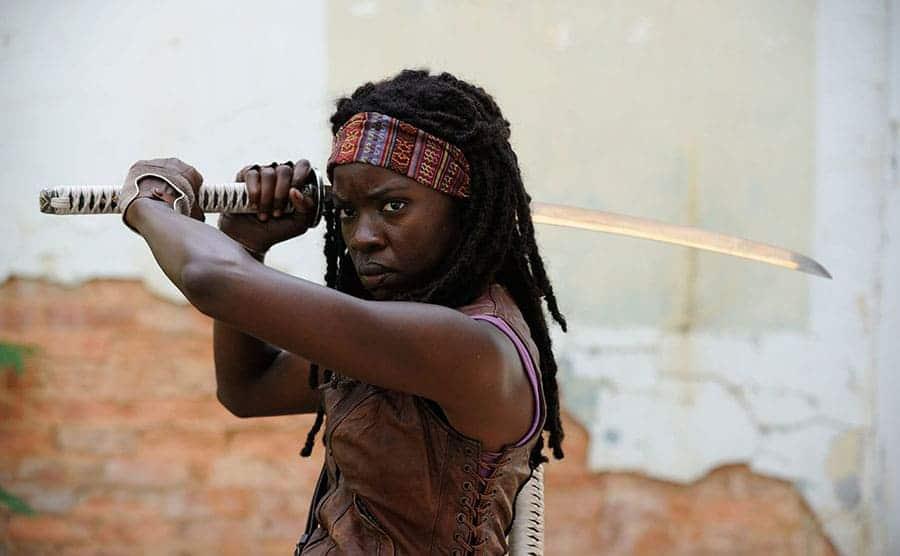 Danai Gurira holding up a sword