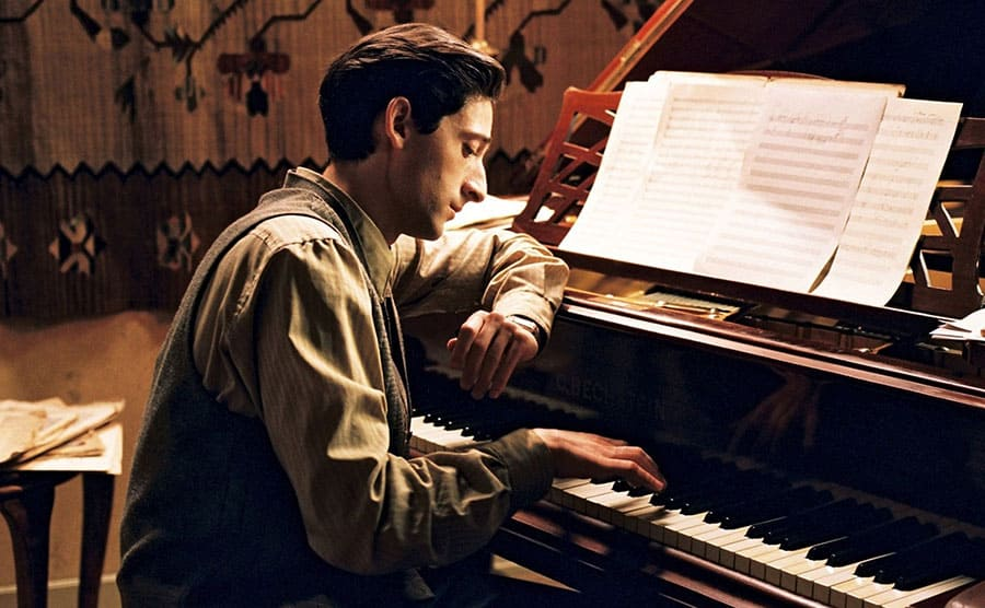 Adrien Brody sitting behind a piano playing