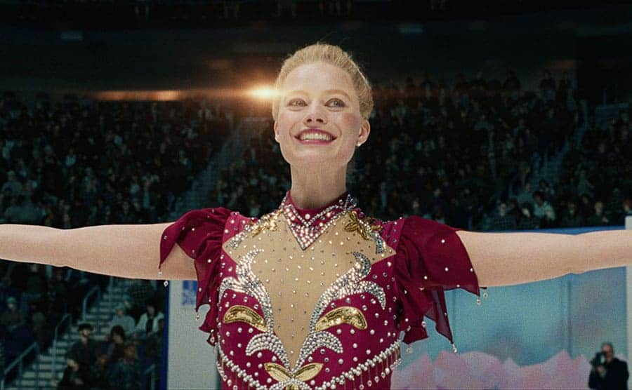 Margot Robbie in the ice rink with her arms spread wearing a figure skating costume