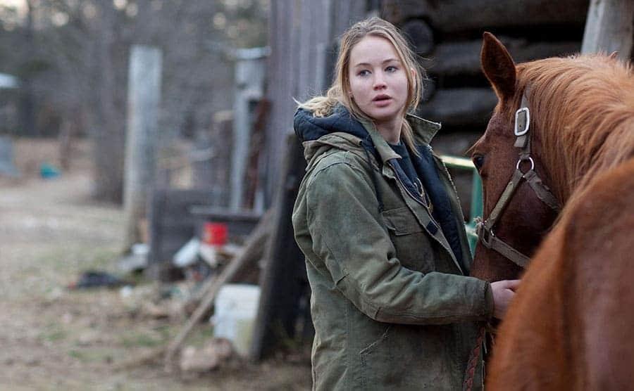 Jennifer Lawrence holding a horses reins in a scene from Winter's Bone