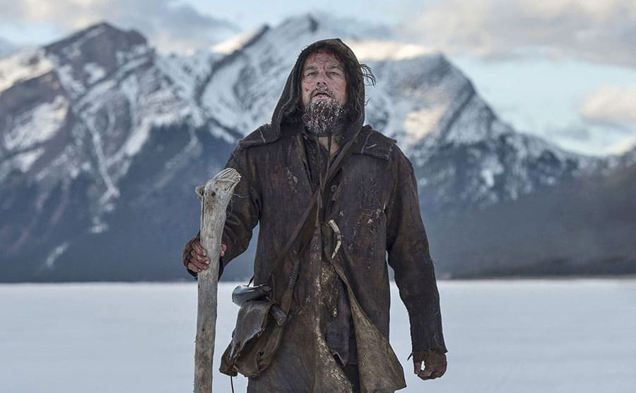 Leonardo DiCaprio in old winter Viking clothing holding a walking stick in front of snow-covered mountains