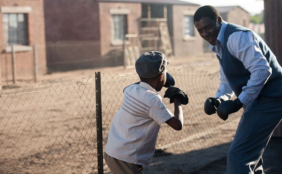 Idris Elba boxing with a young boy outdoors in a scene from the Nelson Mandela film