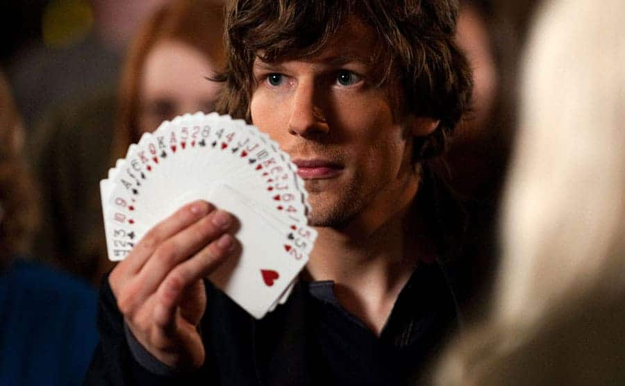 Jesse Eisenberg holding a deck of cards spread out