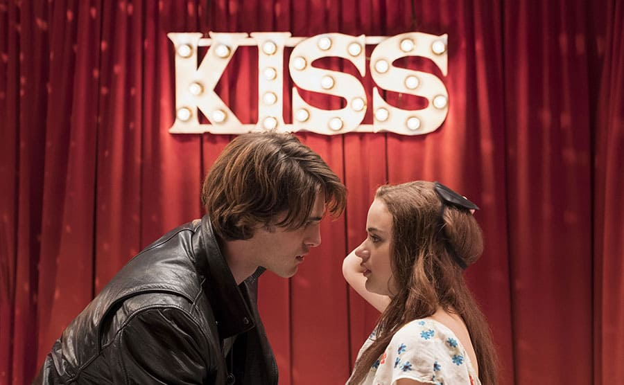 Jacob Elordi and Joey King about to kiss on stage with a sign behind them that says 'KISS'