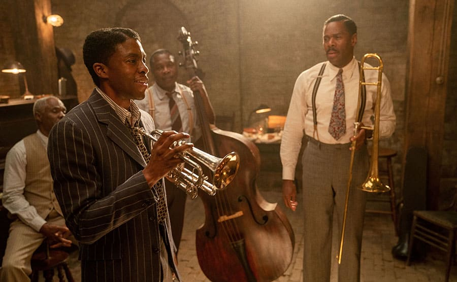Chadwick Boseman holding a trumpet with other actors and instruments around him