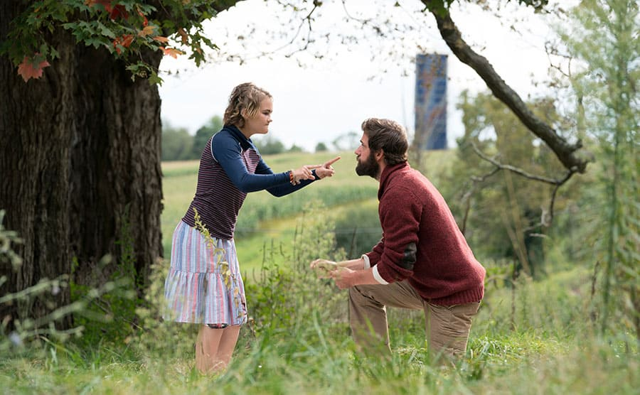 Millicent Simmonds signing for John Krasinski in a woodsy area