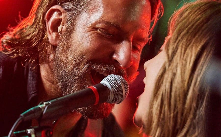 Bradley Cooper singing into the microphone with part of Lady Gaga's face in the image