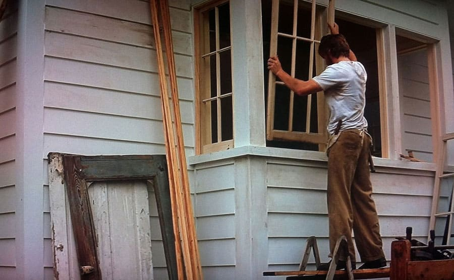 Ryan Gosling putting a wooden window frame in place