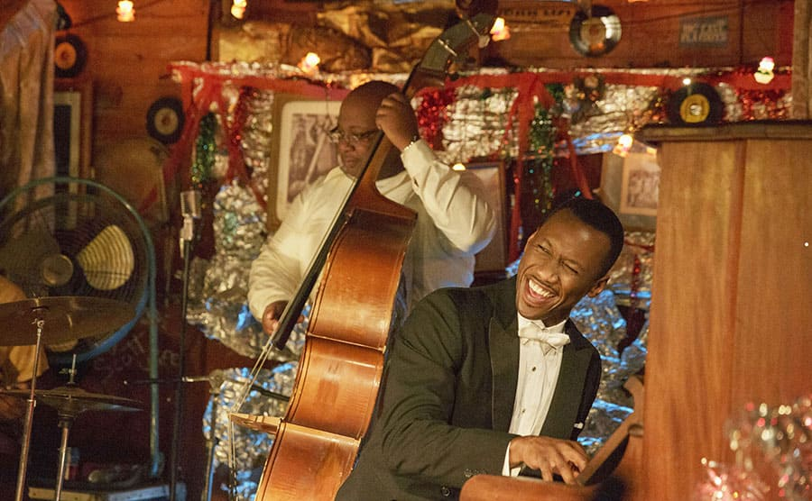 Mahershala Ali playing the piano in a scene from Green Book
