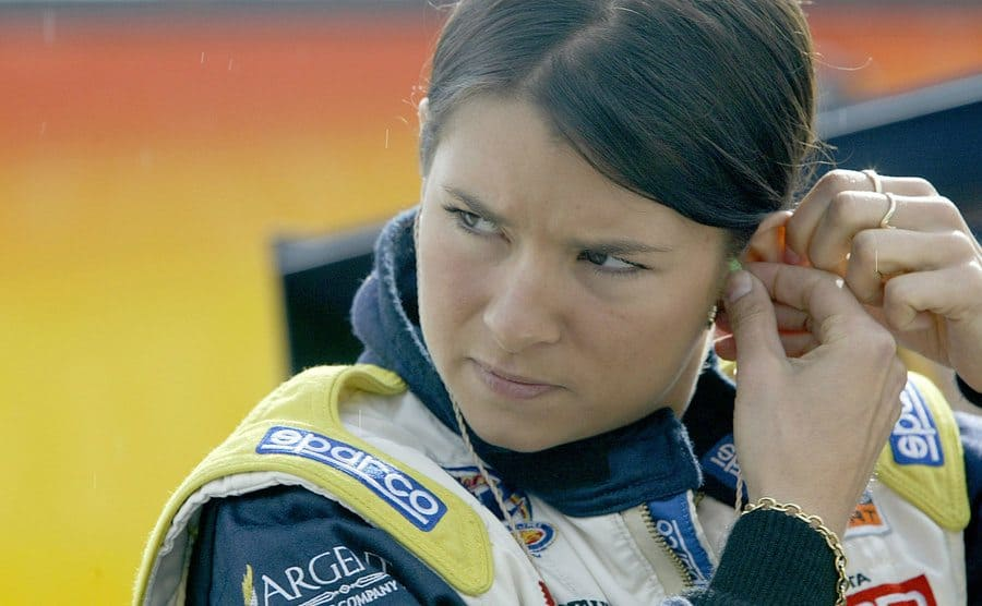 Danica Patrick adjusting her earpiece in racecar gear