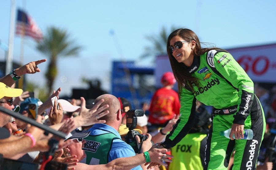 Danica Patrick high-fiving fans while wearing her racing suit